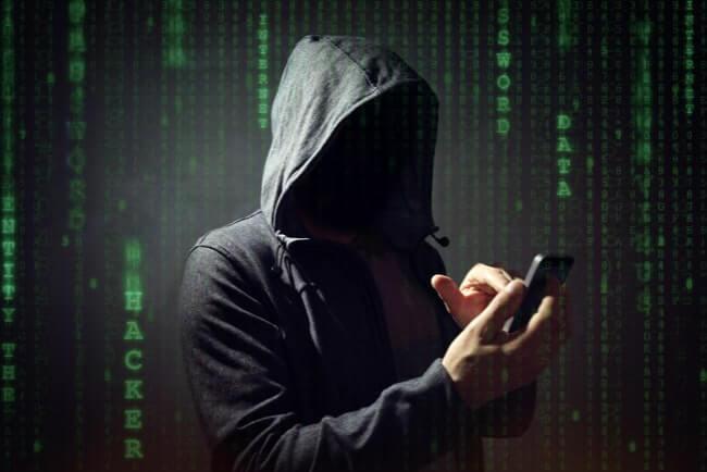 Man med svart huva tröja och luvan uppdragen knappar på en mobiltelefon